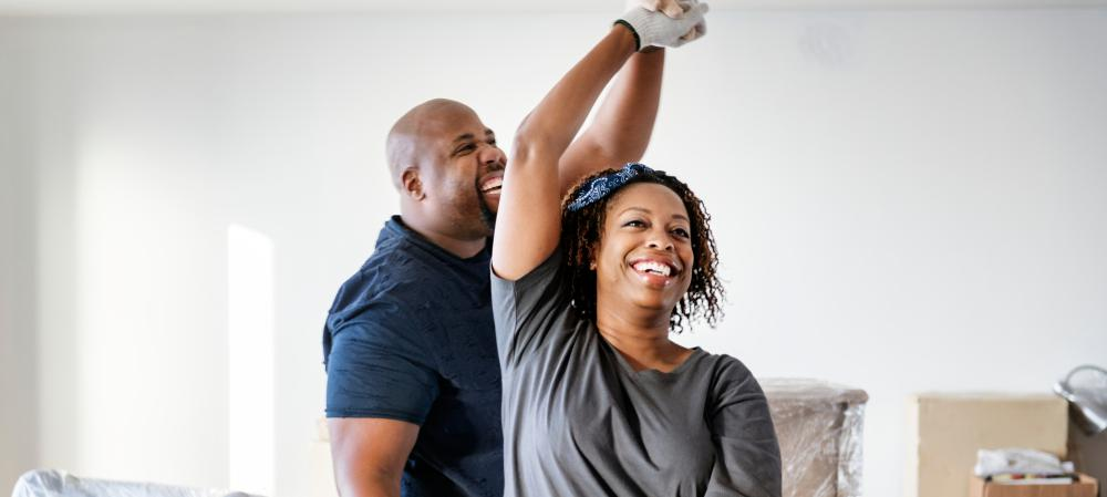A middle-aged african american couple dancing at home